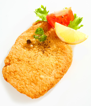Close up view of the crispy golden surface of a pan fried escalope of veal in breadcrumbs with lemon, tomato and parsley on a white background