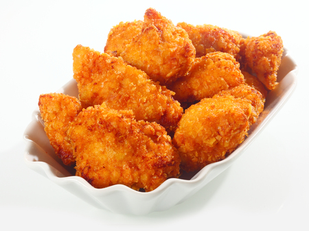 deep fried: Golden crisp fried crumbed chicken nuggets served in a fluted dish as an appetizer or finger food on a white background