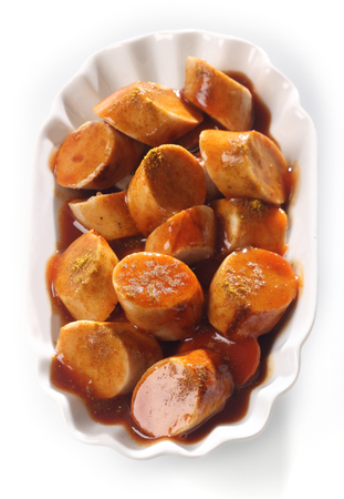 bbq sauce: Overhead view of a dish of sliced grilled spicy Currywurst in tomato or BBQ sauce