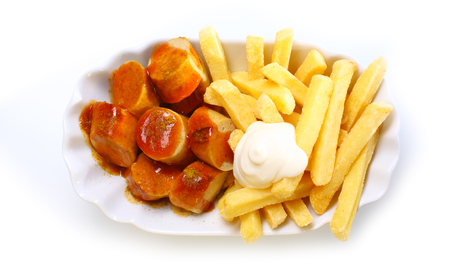 ovenbaked: Slices of grilled smoked sausage and crisp golden French fries topped with mayonnaise in a fluted white dish, over head view on a white background Stock Photo