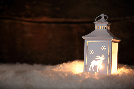 greeting: Christmas lantern with a decorative cut out pattern of a reindeer standing on a bed of fresh winter snow glowing in the night as a welcoming light, with copyspace for your seasonal greeting
