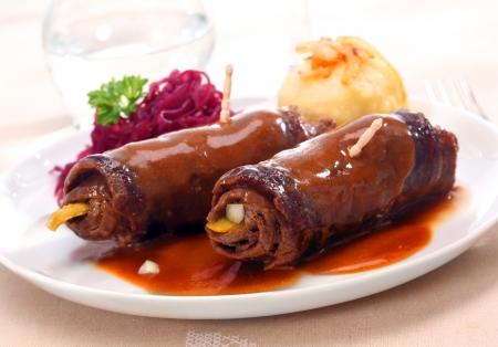 얇게 썰어 진 쇠고기 또는 송아지 고기로 만든 2 개의 맛있는 요리 룰라 드는 야채 나 피클 조각을 채우고 마리 네이드 또는 소스로 오븐에서 찐다.