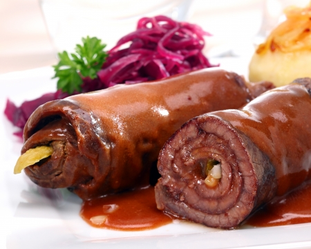 roulade: Close up of the rolled ends of two beef roulades with a rich brown sauce served on a white plate with vegetables Stock Photo