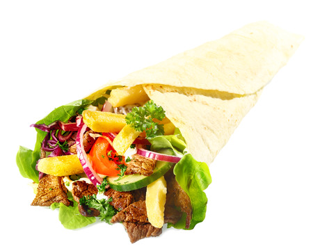 Delicious Lahmacun or tortilla filled with meat, fried potato chips and fresh mixed leafy green salad on a white background