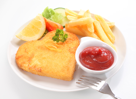 Romantic heart shaped schnitzel in crispy golden friend breadcrumbs served with French fried potato chips and fresh mixed salad with a dish of ketchup on the side photo