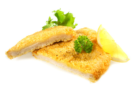 schnitzel: Delicious golden deep fried crumbed chicken or pork fillet cut through to expose the meat garnished with parsley and lemon
