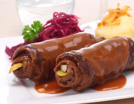 comida alemana: aceitunas de carne que muestran la carne enrollada en rodajas finas y el relleno, servido con verduras Foto de archivo