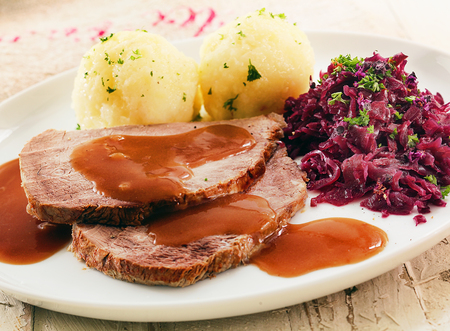 red cooked: Sauerkraut made from red cabbage, potatoes , sliced meat and gravy served on plate, close up view