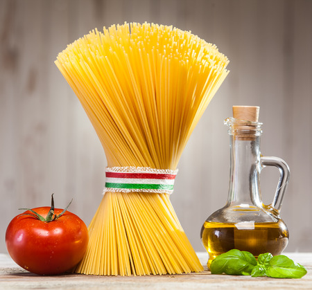 Bundle of uncooked dried Italian spaghetti tied with a ribbon in the colours of the national flag  on a kitchen counter with fresh basil leaves, tomato and a jar of olive oil photo