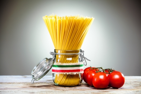 Uncooked dried Italian spaghetti tied with a ribbon in the colours of the national flag - red, white and green - standing in a glass jar with fresh ripe red tomatoes alongside photo