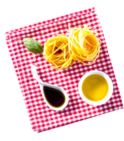 twirled: Overhead view of a checked red and white country napkin with uncooked fettucini pasta with olive oil, soy sauce and basil ready to prepare an Italian pasta dish Stock Photo