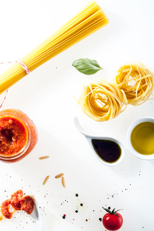 Overhead view of uncooked Italian spaghetti and fettucini with fresh ingredients photo