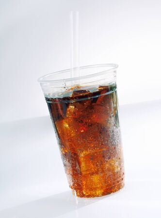carbonated: Glass of iced carbonated soda drink served as a takeaway with a straw