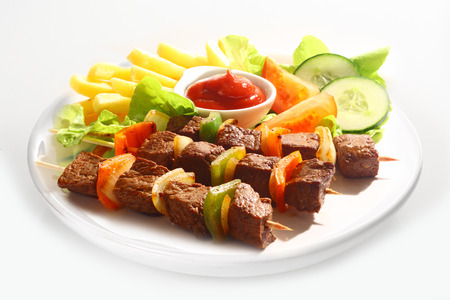 Three grilled beef and sweet pepper kebabs served on a plain white plate with french fries, tomato ketchup and mixed salad Stock Photo - 24286502