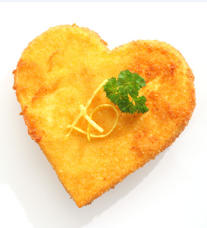 Close-up of tasty breaded fried cheese in heart shape, garnished with parsley photo