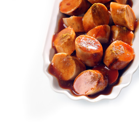 fluted: Close up high angle view of slices of grilled smoked sausage in BBQ sauce in a small fluted dish  Stock Photo