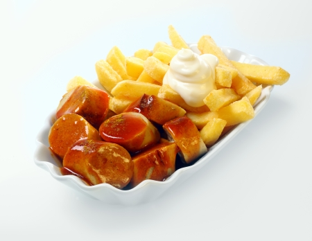 Currywurst served in a dish with golden deep fried potato chips topped with mayonnaise, over white Banco de Imagens