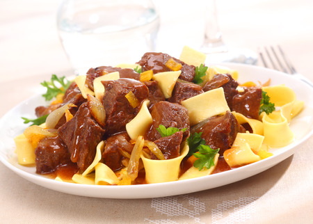 goulash: Serving on a plate of beef goulash, a stew that originated in Hungary, served with noodles and garnished with fresh chopped parsley