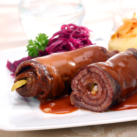 thinly: Two healthy lean beef roulades with thinly sliced meat rolled around a vegetable or pickle filling and served with cooked vegetables, close up view Stock Photo