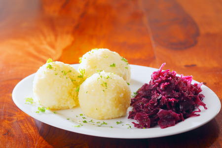 red cabbage: Three cooked potato balls and sauerkraut made from fermented red cabbage served on a side plate as an accompaniment to a meal