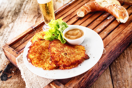 lunch tray: Potato fritters, pretzel and a beer served on a rustic wooden tray for a traditional German pub lunch or snack Stock Photo