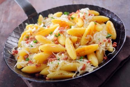 comida alemana: Fritos albóndigas y fideos, conocido como schnupfnudeln, una receta tradicional alemana en una sartén de patatas en forma de dedos