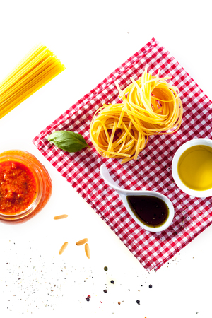 tomato paste: Ingredients for healthy Italian cuisine with uncooked spaghetti and fettucini pastas, soy sauce, olive oil , fresh basil and tomato paste on a red and white checked napkin