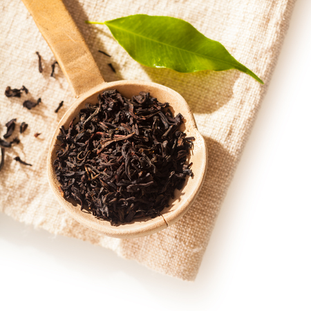 Close up overhead view of a small rustic wooden spoon filled with loose dried shredded tea leaves Stok Fotoğraf - 24905662