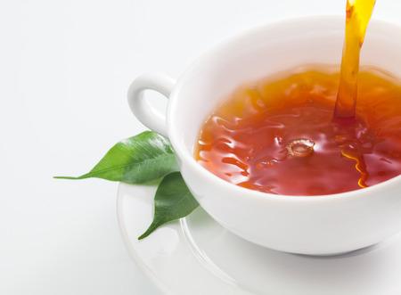 誰かが茶葉新鮮な緑茶と白いカップ プレーンにさわやかなカップを注ぐのクローズ アップ表示 写真素材