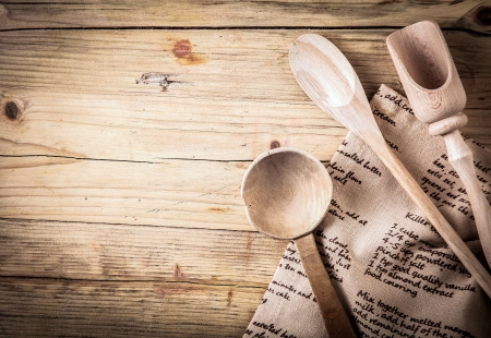 ladle: Rustic cooking utensils with a wooden spoon, ladle and scoop lying on a folded cloth with a recipe on it on an old cracked wooden table with vignetting and copyspace