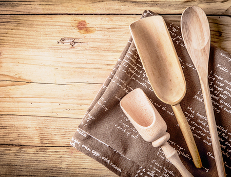 writing implements: Rustic cooking utensils with a wooden spoon and two handcarved rustic scoops lying on a folded piece of hessian on a wooden counter top in a rural kitchen