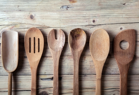 implements: Row of assorted old wooden kitchen utensils lying on a grungy cracked wooden surface in a country kitchen Stock Photo
