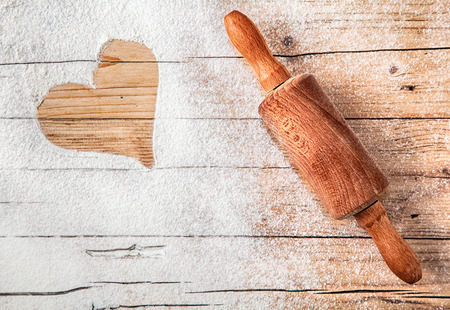 baking ingredients: Heart drawn in scattered flour alongside an old wooden rolling pin depicting love