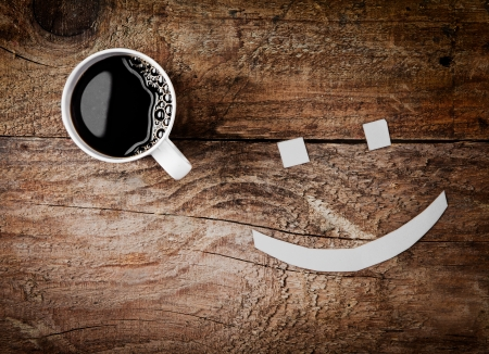 Overhead view of a cup of hot strong black espresso coffee with a smiling face with sugar cube eyes on a rough textured wooden background Stock Photo