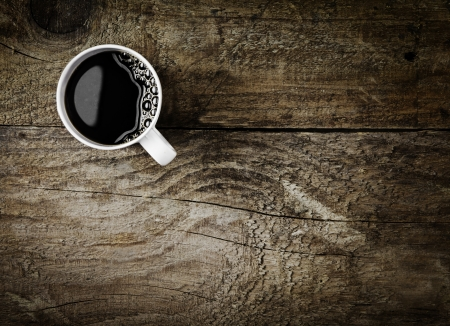 Overhead view of a freshly brewed mug of espresso coffee on rustic wooden background with woodgrain texture and cracks, with copyspace photo