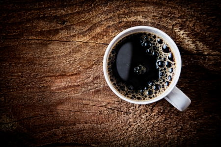 overhead view: Close up overhead view of a cup of strong frothy espresso coffee on a rough textured wooden surface with dark vignetting and a highlight around the mug, with copyspace