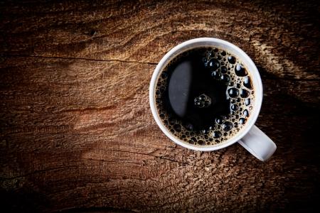 liggande: Närbild ovanifrån av en kopp starkt skummande espressokaffe på en grov texturerad träyta med mörk vinjettering och en höjdpunkt runt om råna, med copy Stockfoto