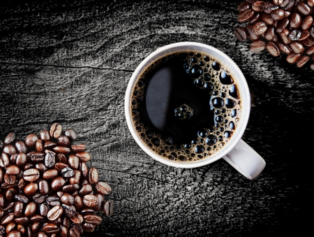 frothy: Full roast coffee beans piled on a rough rustic wooden surface with a cup of freshly brewed espresso coffee with frothy bubbles, close up overhead view