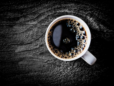 addictive: Close up view of a white mug of fresh full roast filter coffee or espresso with frothy bubbles on a grungy weathered wooden surface with vignetting and copyspace