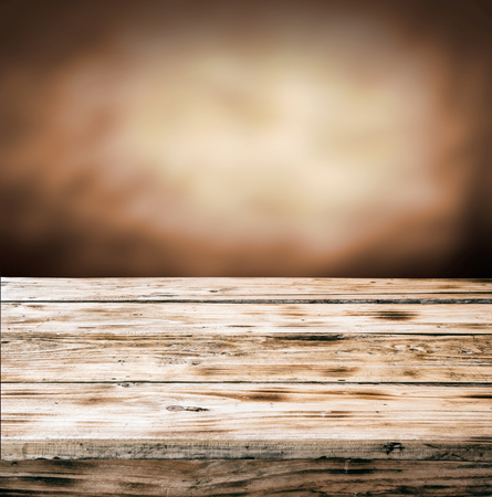 Old empty rustic grunge wooden table top against a blurred brown background with copyspace