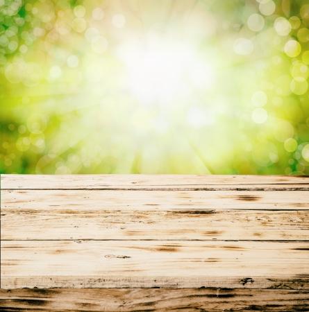 Oude lege rustieke grunge houten tafelblad buiten in de natuur tegen een onscherpe achtergrond van gebladerte en hemel met copyspace