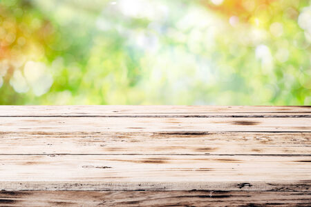 backgorund: Old empty rustic grunge wooden table top against a blurred green blurred outdoor backgorund with copyspace Stock Photo