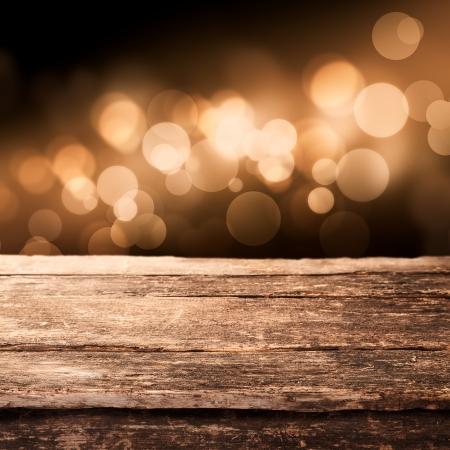 боке: Старый выветривания деревянную доску или загородном столешницу со сверкающим боке золотых партийных огней на заднем плане