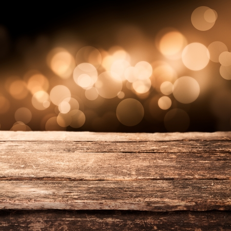 blur: Old weathered wooden board or rustic table top with a sparkling bokeh of golden party lights in the background