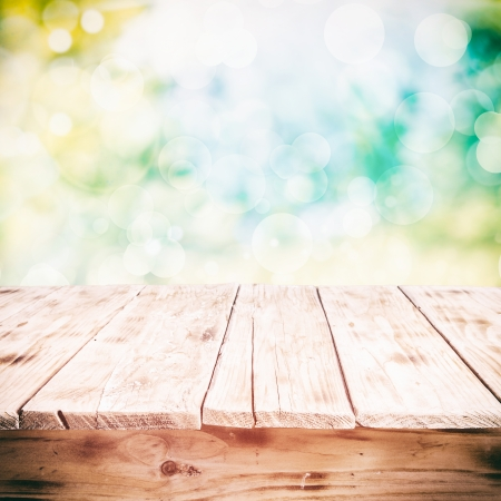 product placement: Old weathered cracked wooden table in a sunny summer garden with a high key background Stock Photo