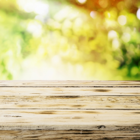 product placement: Closeup of the top of an empty wooden table in a country garden