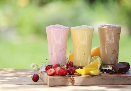 Three fruit or choclate smoothies or milkshakes with fresh organic ingredients including strawberries, cherries, citrus, coffee beans and chocolate blended with yoghurt or icecream photo
