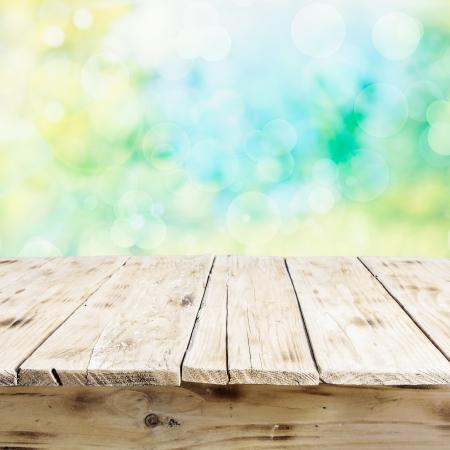 Lege oude houten tafel met een verweerde rustieke oppervlak bekeken lage hoek voor product plaatsing tegen een hoge sleutel frisse buitenlucht zonovergoten achtergrond Stockfoto