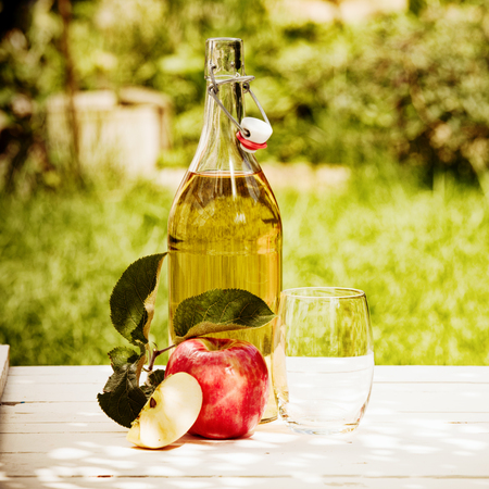 Bottled fresh apple juice served in the garden with a juicy red apple and glass under the shade of a tree Stockfoto