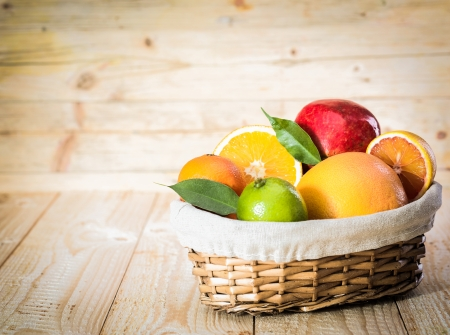 Colourful wicker basket of assorted tropical fruit with a lime, grapefruit, oranges and an apple in a country kitchen on wooden boards Stock Photo